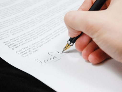Image of signing a document. Technical translation agency