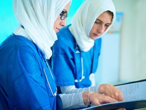 Two arabic women in medical scrubs and headscarves working on a translation