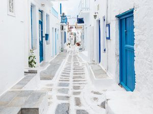 Looking down a narrow whitewashed street with blue doors