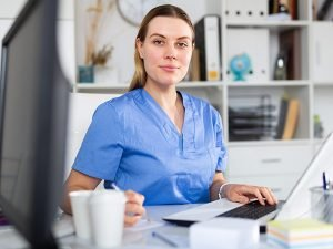 A young woman in medical scrubs sitting at a laptop