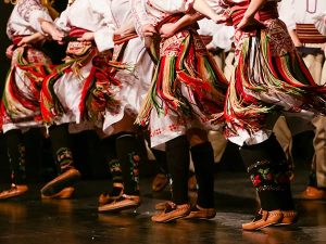 The feet and skirts of a row of dancers in Serbia