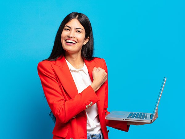A young, friendly looking Spanish woman with a laptop